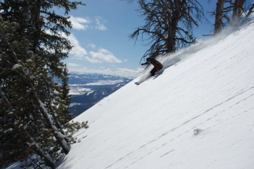 person sliding on snow-covered downhill with snowboard during daytime
