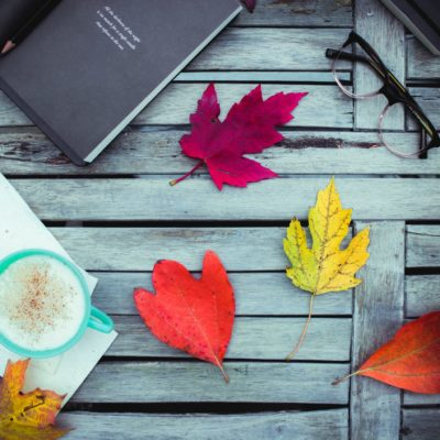 assorted-color leaves near eyeglasses, books, and green ceramic mug